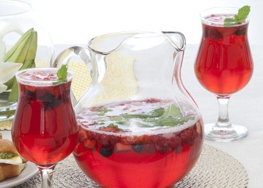 Вино, ром, газированную воду смешать с сахаром, добавить нарезанные тонкими кружочками абрикосы, смородиновый сок и целые ягоды клубники (большие разрезать пополам).  Подавать в стеклянных кувшинах со льдом.