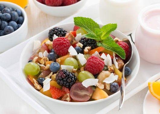 Берем по 200 г малины и ежевики, очищаем их от хвостиков. Удаляем кожуру с киви, вынимаем косточки из 6 абрикосов, снимаем с веточки виноград без косточек и режем на половинки. Все фрукты нарезаем кубиками и соединяем с ягодами. Раскладываем салат по креманкам и украшаем листьями мяты.