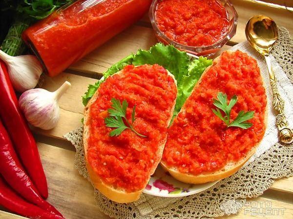 5 кг спелых помидоров, 5-6 головок чеснока, 100 г соли, 1 острый перец, 6 больших корней хрена, сладкий перец. Все пропустить через мясорубку, размешать и разложить по емкостям, хранить в холодильнике.