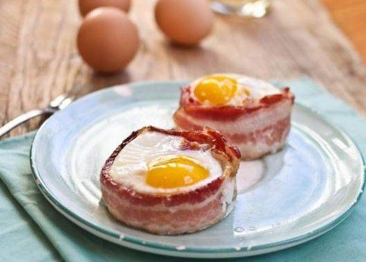 Для приготовления вам понадобятся корзинки для маффинов, бекон и яйца. Сверните в корзинке тонкие ломтики бекона, разбейте в середину корзинки яйцо и запеките всё это в духовке.