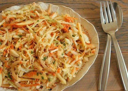Капусту порезать, посолить, перетереть руками до появления сока, чтобы она стала мягче. Натереть на терке морковь. Мелко порезать яблоко. Все перемешать. В чашку с водой добавить сахар, уксус, хорошо перемешать и соединить с салатом.