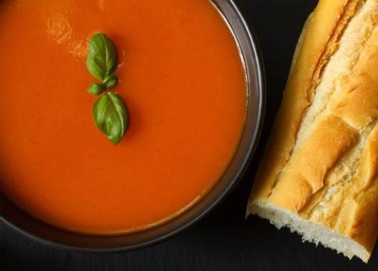 Лук очищаем и разрезаем на 4 части. Чеснок не чистим, а только разделяем на зубчики. Перцы смазываем оливковым маслом и выкладываем на противень. На другой противень кладем помидоры, лук и чеснок, сбрызгиваем сверху оливковым маслом, накрываем фольгой. Помещаем все овощи в предварительно разогретую до 180 градусов духовку и запекаем 35–40 минут. Овощи охлаждаем. Затем снимаем кожицу с перцев и удаляем семена. Запеченный чеснок чистим. Помещаем все ингредиенты в блендер, солим и перчим, добавляем по вкусу табаско и базилик, заливаем овощным бульоном и взбиваем на максимальной скорости до однородной консистенции.