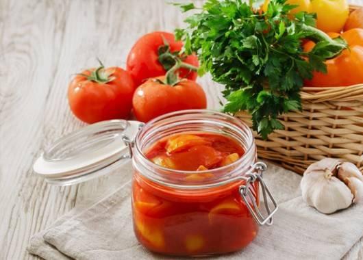 Промываем, чистим от семян и разрезаем перец и томаты на части. Перед приготовлением лечо помидоры стоит очистить от шкурки. Для этого держим их в кипятке 3—4 минуты, это облегчит процесс. По желанию томаты можно пропустить через мясорубку. Лук чистим, нарезаем полукольцами и обжариваем на масле до золотистого цвета. Выкладываем лук в большую емкость и добавляем помидоры, солим по вкусу. Тушим все 15—20 минут. Постоянно помешиваем. К помидорам добавляем перец и тушим 5 минут при закрытой крышке. После снимаем крышку и тушим еще 10 минут, не забывая помешивать. Чистим чеснок, измельчаем и добавляем в общую массу. Следом добавляем уксус и сахар. Тушим около 15—20 минут. Добавляем в блюдо паприку, черный перец, измельченную зелень, хорошо перемешиваем и готовим около 10 минут.