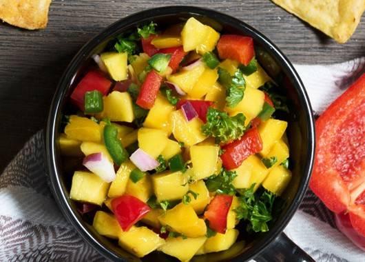 Манго очищаем и нарезаем мякоть кубиками. Очищаем и нарезаем лук, а также болгарский перец. Выкладываем манго, лук и перец в салатник, солим и перчим, поливаем соком лайма. Перемешиваем и посыпаем нарубленной петрушкой. Даем салату настояться 10 минут перед подачей.