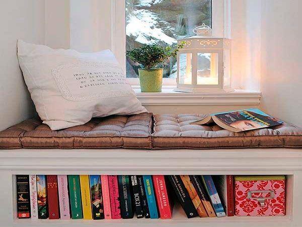 Дизайн окна с подоконником оформлен в виде небольшой домашней библиотеки, а мягкие подушки дадут возможность почитать, при свете оригинального фонаря.