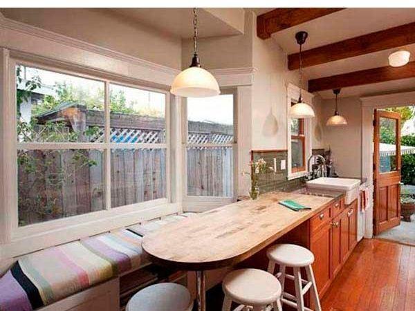 Дизайн подоконника стилизован под большую и удобную лавку, примыкающую к кухонному гарнитуру, а лампа с широким абажуром поможет осветить все пространство, что для кухни довольно важно.