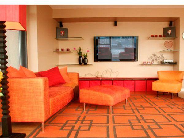 Напольное покрытие и мебель очень близки по цветовой гамме, но монохромность сработала благодаря форме всех компонентов – квадрат, тёплым стенам и мягким акцентным креслам.