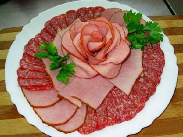 Очень оригинальный вариант – сделать из мясных изделий цветы, которые станут отличным украшением закуски. Для этого нужно просто скрутить кусочки мяса или колбасы, придавая форму цветка.