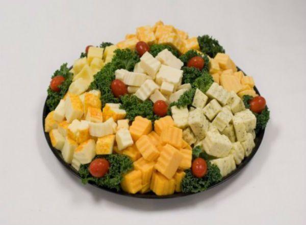 Украшением нарезки из сыра может быть виноград, киви, апельсины, клюква, различная зелень, помидоры черри, оливки и маслины.