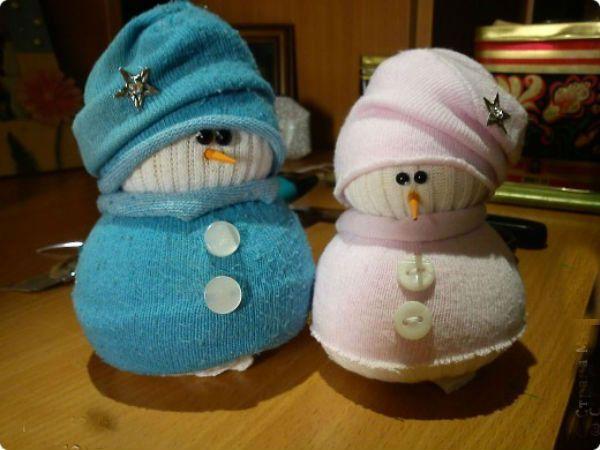 Снеговички из носков делаются совсем несложно, а выглядят они просто очаровашками. Берем белый носок, насыпам наполнитель (любую крупу или соль), завязываем верх. А из цветного носка делаем одежку.