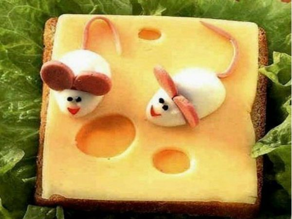 А как вам такие мышата, прибежавшие попробовать кусочек сыра? Для приготовления мышек яйцо разрезаем пополам, в качестве ушей используем кружочки тонкой сосиски, глазки - перец горошком.