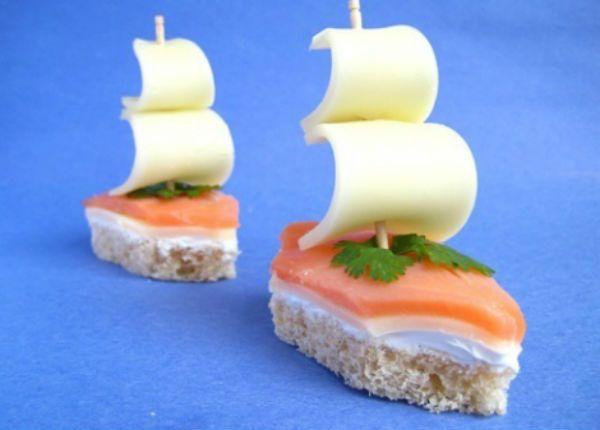 """Бутерброды """"Королевский флот"""", приготовленный из красной рыбы и мягкого белого сыра. Просто вырезаем хлеб по форме кораблика, смазываем маслом, кладем кусочек сыра и кусочек рыбы. На мачту-шпажку крепим паруса - кусочки сыра."""