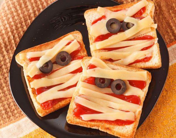 Для приготовления бутербродов «Мумия» хлеб смазываем кетчупом, из кружочков маслин делаем глазки, а «лицо» бутерброда «заматываем» тонко нарезанными полосками сыра.