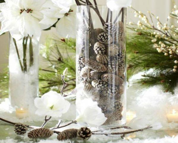 Оригинальным новогодним украшением станет прозрачный узкий стакан, наполненный небольшими шишками. Их можно даже затонировать белой краской.