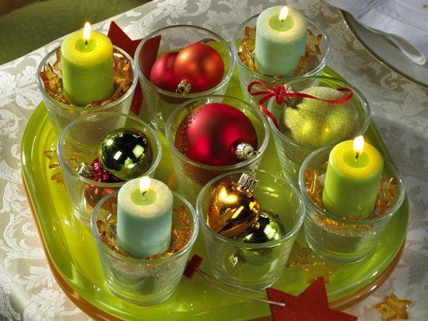 Свечи можно поставить в прозрачные или цветные стаканчики, а рядом - еловые веточки, шишки или елочные игрушки.