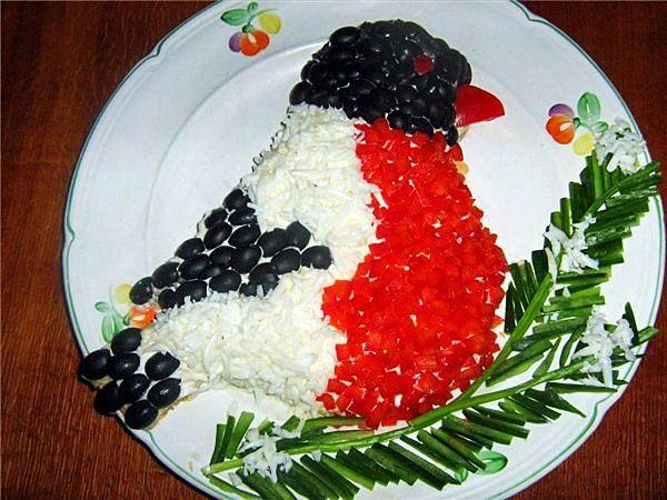 Яркий салат, выложенный в форме снегиря. Голова, крылья и хвост из маслин, тело из болгарского перца и яичного белка. Еловая веточка из зеленого лука и огурца.