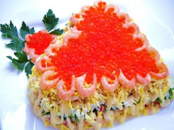 Салат с морепродуктами, выложенный в форме сердца и украшенный красной икрой и креветками, смотрится очень ярко и аппетитно.