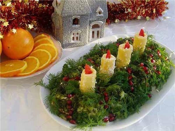 Салат со свечами украшен укропом и зернами граната. Свечки сделаны из твердого сыра (можно сделать из вареного картофеля), язычки пламени из болгарского перца.