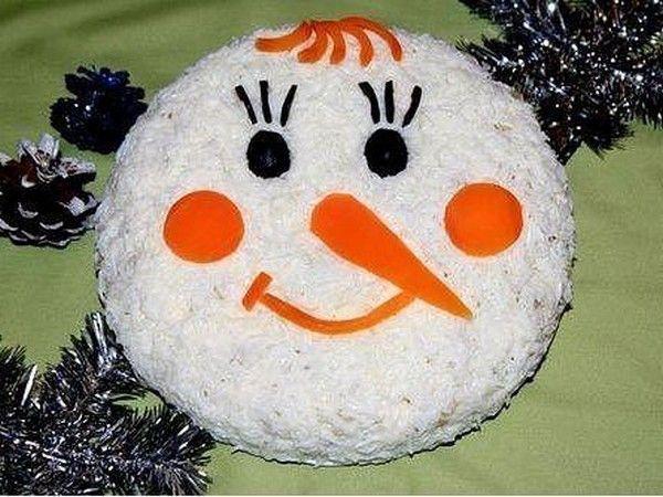 Веселый салат в форме головы снеговика. Верхний слой из яичного белка, щеки, нос, рот и челка из моркови, глаза из маслин.