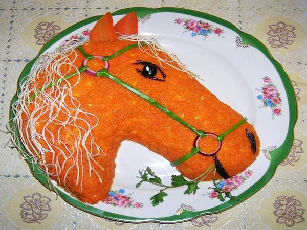 Еще одна лошадка, но уже огненная. Верхний слой выложен из вареной моркови. Уздечка из лука, глаза, нос и рот из маслин, грива из сыра «Косичка».