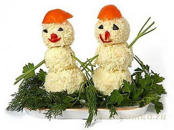 Братья снеговики. Тертый сыр с чесноком, выложенный в форме снеговиков. Снеговики украшены морковью, болгарским перцем, маслинами и зеленью.