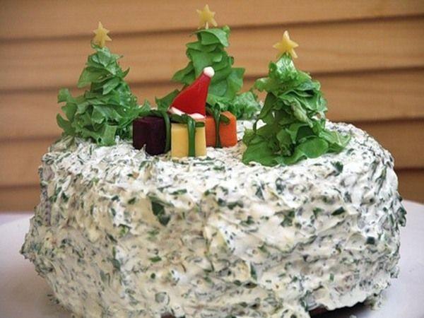 Салат украшен в виде новогодней поляны. Елки сделаны из листьев салата, звездочки из сыра, коробки с подарками вырезаны из моркови, свеклы, сыра и украшены луковыми лентами.