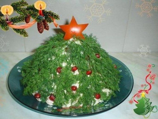 Салат в форме праздничной елки. Ветви елки выложены из укропа, звезда вырезана из болгарского перца, елочные украшения из зерен граната.