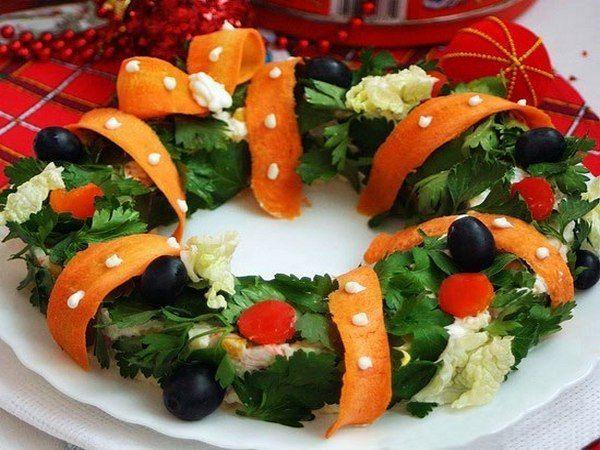 Салат в виде рождественского венка смотрится очень красиво. Венок украшен петрушкой, маслинами, лентой из моркови.