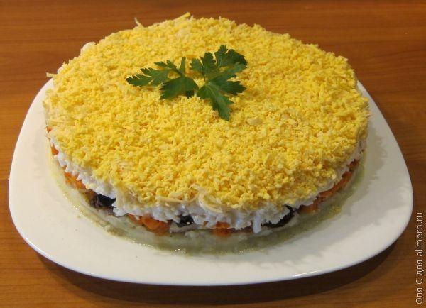 «Торт-салат с печенью трески». Рецепт: Оля С. Ингредиенты: картофель, морковь, яйца, печень трески, лук, твердый сыр, чернослив, соль, перец. Заправка: майонез. Украшение: зелень.