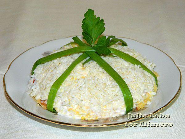 Салат «Новогодний подарок». Рецепт: Юлия Леба. Ингредиенты: яйца, картофель, докторская колбаса, сыр, консервированный салат из помидоров и болгарского перца, чеснок, соль, специи. Заправка: майонез. Украшение: зеленый лук.
