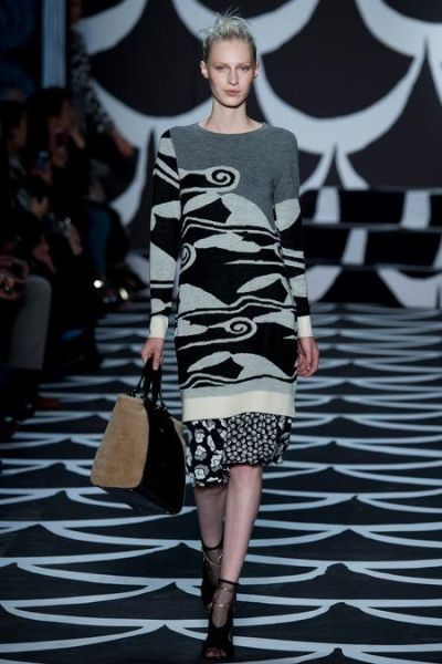 Свитер-туника с крупным ассиметричным рисунком, выполнен в сдержанной черно-серой гамме. Главный тренд сезона – крупные детали. Будь то узор, аппликация или объемный крой.