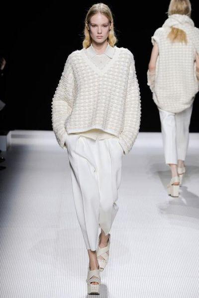 Немножко укороченная шерстяная модель с V-образным вырезом. Белый цвет и рельефный узор отлично подойдут девушкам с хорошей фигурой.  Такой свитер как нельзя лучше подчеркнет изящество и женственность своей обладательницы.