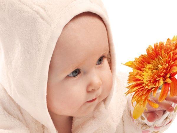 Съемка крупным планом делает фотографию «живой» и трогательной.  Яркий цветок, привлекающий внимание малыша, дает возможность запечатлеть кроху с выражением неподдельного интереса в глазах.