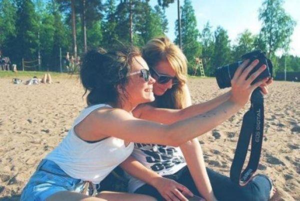 Девушки с фотоаппаратом.  Снимок смотрится так, словно мы за ними подглядываем.  Еще можно сделать иначе - взять 2 камеры, стать напротив друг друга и фотографировать.