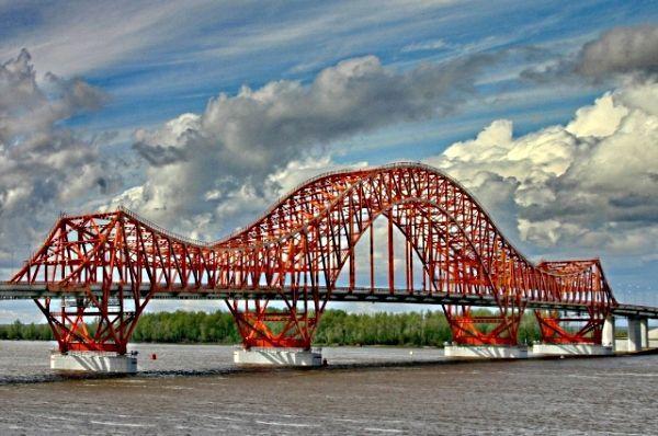 А вот автомобильный мост на реке Иртыш в Ханты-Мансийске. Называется он «Красный дракон», так как немного напоминает мифическое существо, притаившееся на речном берегу.