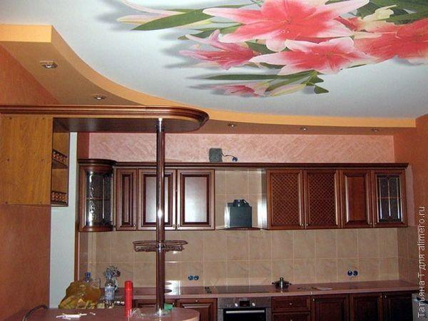 Цветы на кухне, пусть даже это просто принт на потолке, делают ее уютнее. На такой кухне и готовить приятно, и кушать интересно.