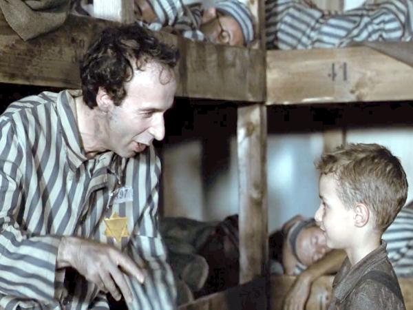 Итальянская трагикомедия «Жизнь прекрасна». Первая часть фильма, это история любви жизнерадостного Гвидо и  школьной учительницы Доры. Вторая часть, трагическое повествование о выживании Гвидо, Доры и их сынишки в застенках  концлагеря.