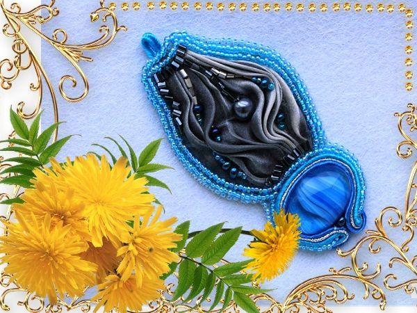 Фантазийный кулон или брошь из ленты шибори черного цвета, украшенная синим кабошоном и голубого оттенка бисером. Дополнительное изящество броши придает кант из трехцветного атласного шнура.