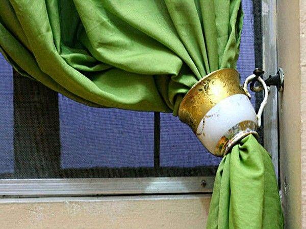 Чашка с выбитым донышком может стать оригинальным подхватом для штор. Острые края вокруг отверстия нужно обработать наждачной бумагой, чтобы они стали гладкими и не цеплялись за ткань.