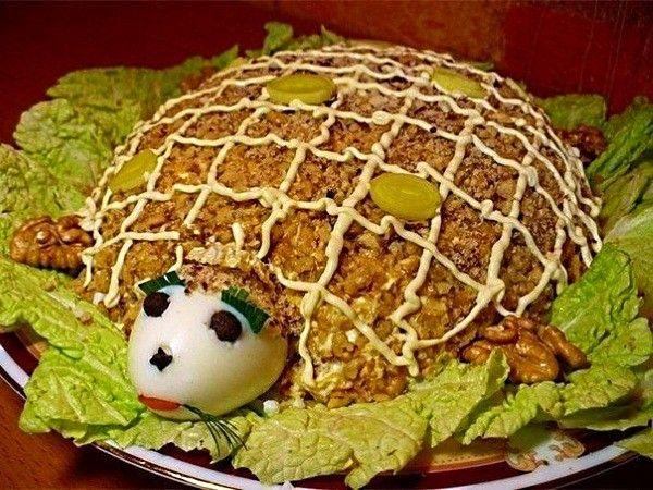 Салат с грецкими орехами, в виде черепахи, мало кого оставит равнодушным. Для имитации панциря, орехи нужно измельчить как можно мельче и нарисовать сеточку майонезом. Для головы отлично подойдет вареное куриное яйцо, а для лапок половинки орехов.