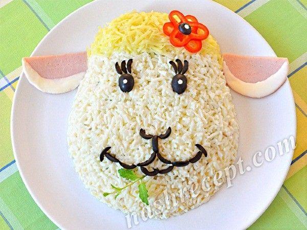 У этой чудесной овечки мордашка из тертых белков. Ушки сделаны из кусочков вареной колбаски, а челка из тертого твердого сыра. Глазки и ротик выложены из кусочков маслин, а цветочек можно соорудить из колечек сладкого перца или помидора.