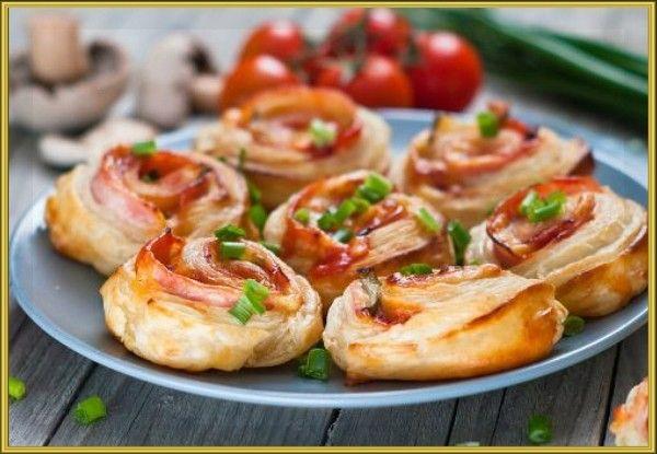 12. Рулеты с сыром и ветчиной. Раскатайте 400 г слоёного теста в прямоугольник размером примерно 30 × 45 сантиметров. Нарежьте тонкими ломтиками 200 г ветчины и 150 г твёрдого сыра. Порубите зелень и чеснок, смешайте их с 1–2 столовыми ложками майонеза и намажьте этим соусом пласт теста, отступив 3–5 сантиметров от края. Равномерно разложите по тесту ветчину и сыр. Несмазанный край оставьте свободным. Сверните рулет так, чтобы эта полоска теста оказалась с внешней стороны. Её можно смочить водой, чтобы плотно запечатать рулет. Разрежьте рулет на куски шириной 4–6 сантиметров. Сверху рулет можно смазать желтком и посыпать маком или кунжутом. Выпекайте 20–25 минут при 180 °С.