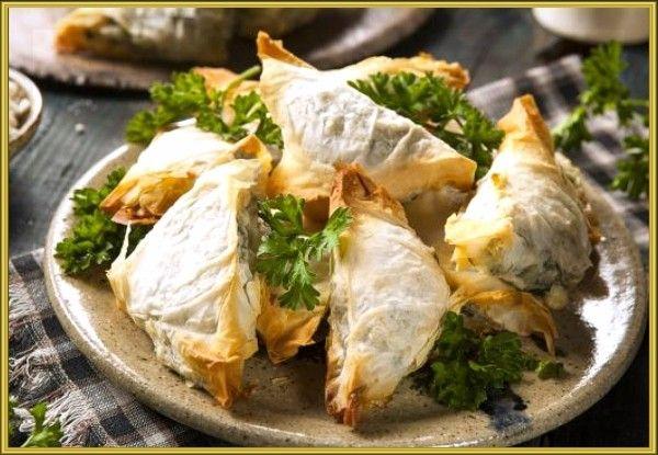 16. Спанакотиропита (традиционный греческий пирог со шпинатом и фетой). Разморозьте, просушите и нарежьте 200 г замороженного шпината. Обжарьте 1 луковицу на оливковом масле до золотистого цвета. В отдельной посуде взбейте 2 яйца и соедините их с 200 г сыра фета. Тщательно перемешайте, добавьте обжаренный лук, мелко рубленую зелень и чеснок. Тонко раскатайте 250 г слоёного теста и нарежьте его квадратами шириной 10–12 сантиметров. Выложите на каждый из них по две столовые ложки начинки. Заверните пирожки треугольниками. Выпекайте пирожки 20–25 минут при 180 °С.