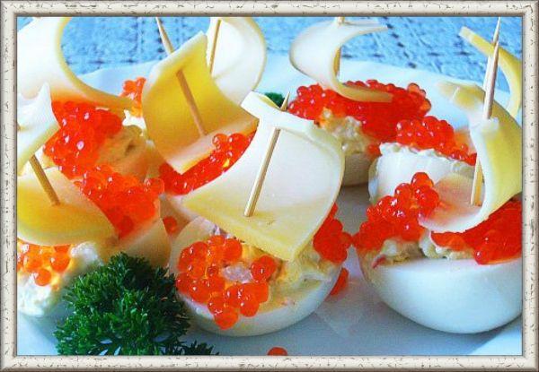 11. Парусники. Соленая сельдь с маринованным луком   яблоко. Нафаршированные половинки яиц украсить красной икрой и парусами из кусочков сыра и зубочисток.