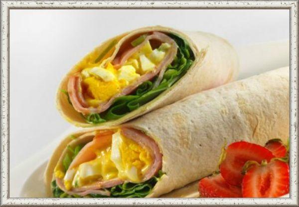 13. Ролл с яйцом. Продукты: лаваш, листья салата, ветчина, 2 яйца, соль и перец - по вкусу. Приготовление: приготовьте яйца методом скрембл (жарьте, постоянно помешивая), посолите и поперчите. Возьмите лаваш. Внутрь положите листья салата, ветчину и готовые яйца. Сверните в трубочку, загнув концы, и разрежьте пополам немного наискосок.
