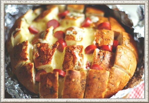 10. Белый пицца-хлеб. Разогрейте духовку. Нарежьте буханку хлеба сначала по длинной стороне, а затем по ширине, чтобы получилась сеточка. Оберните хлеб фольгой и поставьте в духовку на 10 минут. Растопите сливочное масло в микроволновой печи или маленькой кастрюле. Помешивая, добавьте в масло чеснок, тертый сыр и листья тимьяна. Аккуратно приподнимите хлебные кусочки и залейте их соусом. В расщелины хлеба аккуратно положите нарезанные вяленые помидоры и тертый сыр. Выпекайте хлеб 15- 20 минут до золотистой корочки. После выпекания снова посыпьте его тертым сыром.