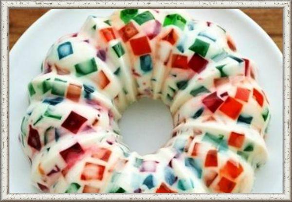 13. Десерт желейный «Битое стекло». Ингредиенты: 3 пачки желе разного цвета - красное, оранжевое, зеленое,  желатин быстрорастворимый – 25-30 г, вода – 50-70 мл, сметана 15% - 400-500 мл, сахар – 1 стакан, ванильный сахар – 1 пачка. Приготовление: В трех емкостях приготовить порошковое желе согласно инструкции. Убрать на холод. Желатин замочить в воде. Сметану, сахар и ванилин смешать. Желатин растворить на водяной бане. Готовое желе порезать кубиками и смешать в одной посуде. Горячий желатин вылить в сметанную смесь, перемешать и вылить к уже готовым желейным кубикам. Аккуратно перемешать вилкой и вынести на холод до полного застывания.