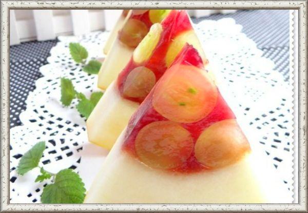 """12. Десерт """"Сочные дольки"""". Ингредиенты: 1 дыня (средняя круглая), виноград (зеленый без косточек) - 250 г, сок свежий вишневый - 250 мл, желатин - 18 г, вода кипяченая - 120 мл, сахар - 60 г.  Приготовление: дыню помыть отрезать верхушку, ложкой удалить семена.  С помощью столовой ложки снять часть мякоти дыни. Заполнить дыню виноградом. Желатин замочить на 30-40 минут в холодной кипяченой воде, добавить сахар и нагреть до полного растворения. Влить процеженный вишневый сок. Залить  дыню вишневым желе, поместить её в холодильник  на ночь.  Нарезать дыню сначала на круги, затем на треугольники."""