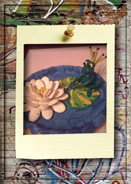 3. Принцесса лягушка. Для ее изготовления понадобится: упаковка пластилина, тыквенные семечки, пластмассовая крышечка от майонезного ведерка, зубочистка.