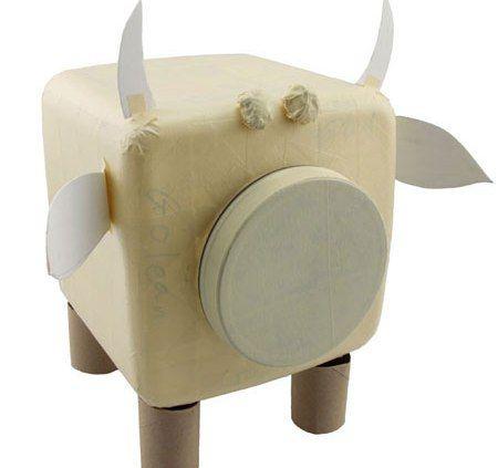 Разрежьте картонные трубки пополам и используйте их в качестве ног. Прикрепите их с помощью клейкой ленты.  Аккуратной обмотайте бумажной клейкой лентой весь контейнер, скройте стыки, где находятся уши, рога и ноги.